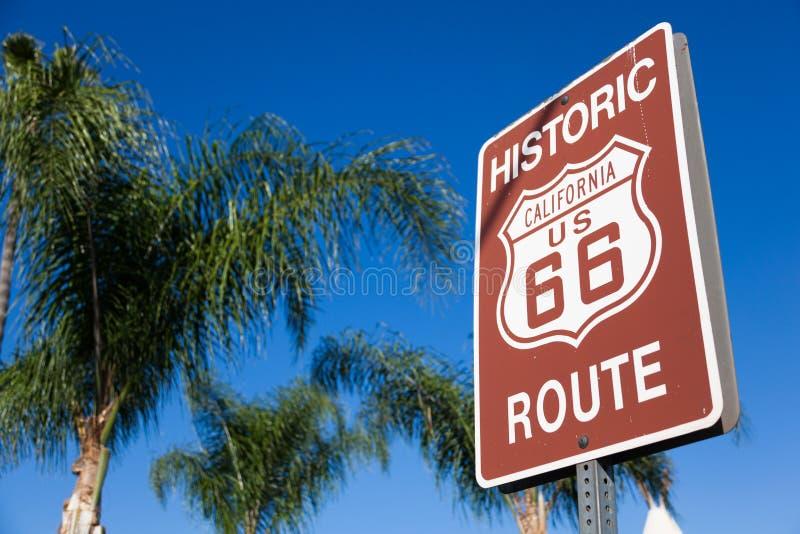 Sinal histórico da estrada da rota 66 com palmeira e um céu azul fotografia de stock