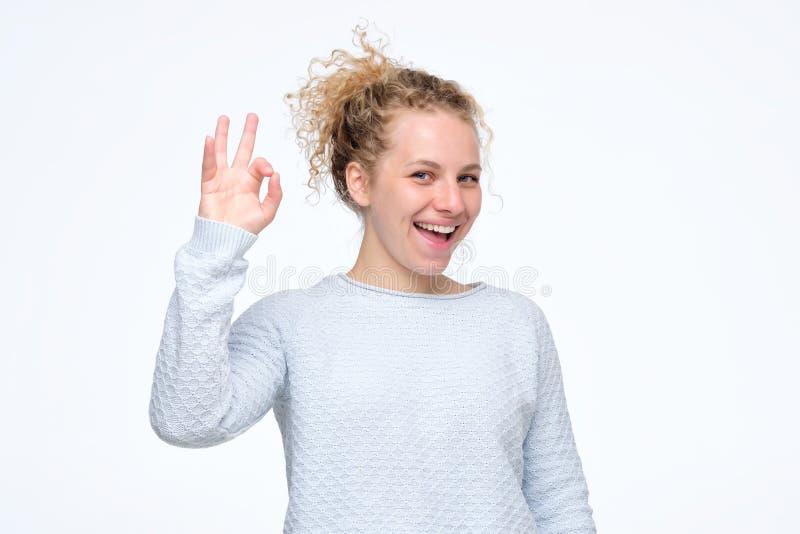 Sinal louro novo atrativo da aprovação da exibição da mulher imagem de stock
