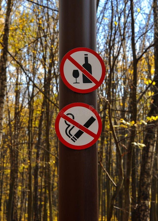 Sinal não beber, para não fumar em um polo no parque fotografia de stock
