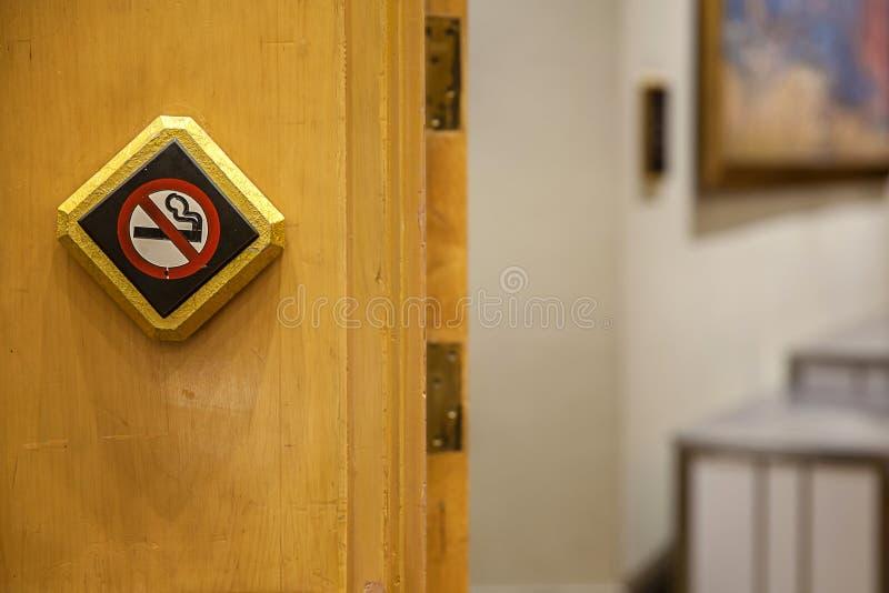 Sinal não fumadores contra uma parede de madeira O sinal defumo branco no assoalho de madeira é um sinal que o viajante está cien imagem de stock