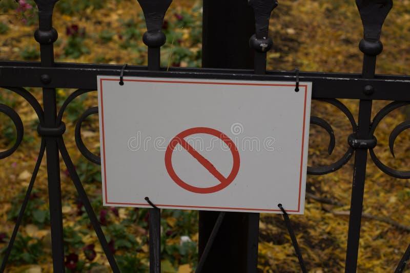sinal não permitido dos cães em um parque em uma etiqueta da cerca fotografia de stock royalty free