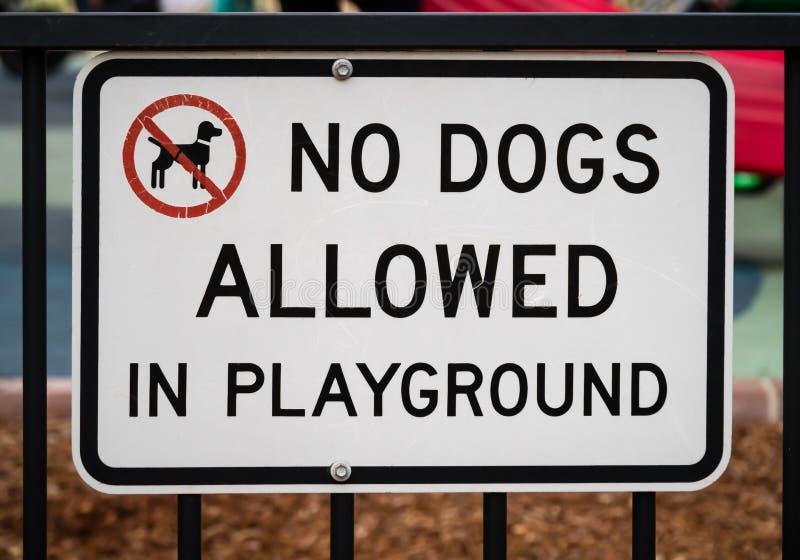 Sinal na cerca com texto NENHUNS CÃES PERMITIDOS NO CAMPO DE JOGOS e no símbolo do cão no círculo vermelho fotografia de stock