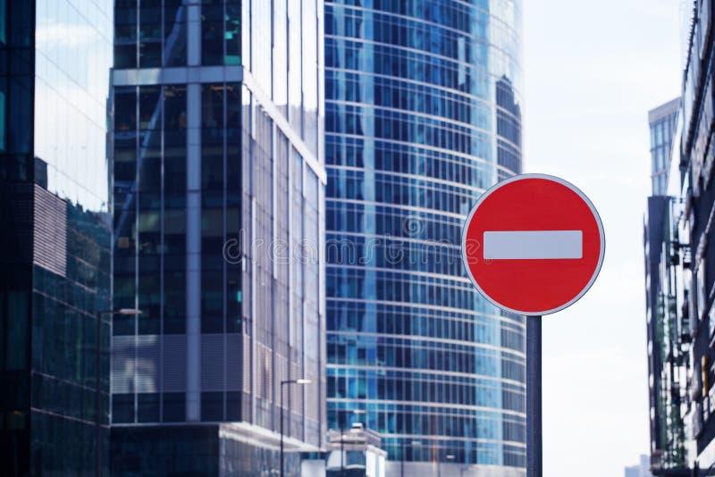 Sinal ou tijolo vermelho da parada da estrada no fim borrado centro de negócios do fundo dos arranha-céus da cidade acima, proibi imagens de stock royalty free