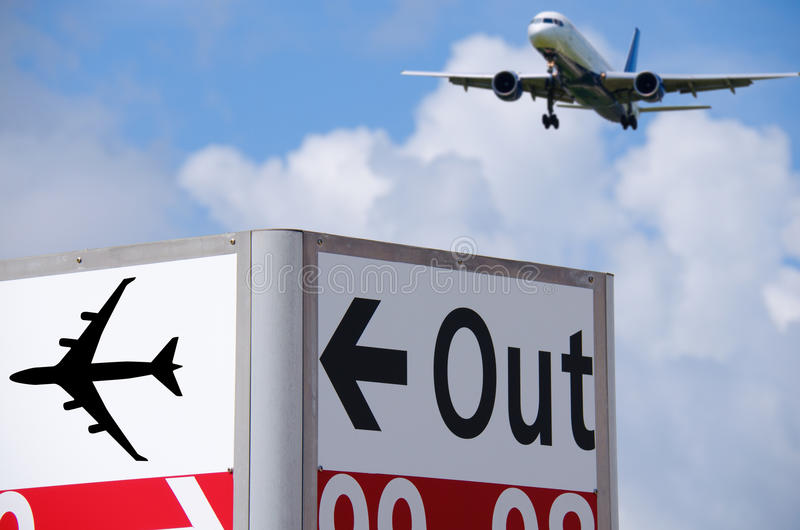 Sinal para fora direcional no aeroporto com parte traseira do plano dentro imagens de stock