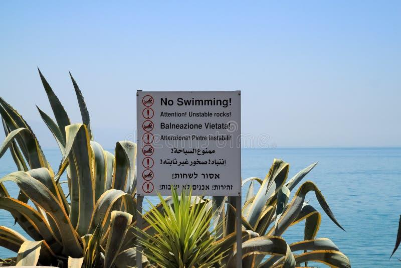 Sinal que não indica 'nenhuma natação! 'em 8 línguas é aninhado entre plantas decorativas da agave ao longo do mar de Galilee fotos de stock