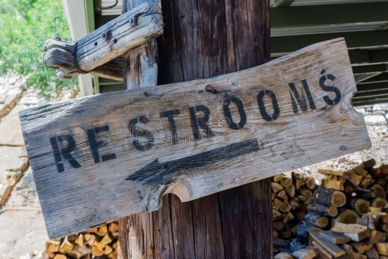 Sinal rústico da placa de madeira em um cargo com escrita preta e seta que aponta ao toalete público imagem de stock royalty free