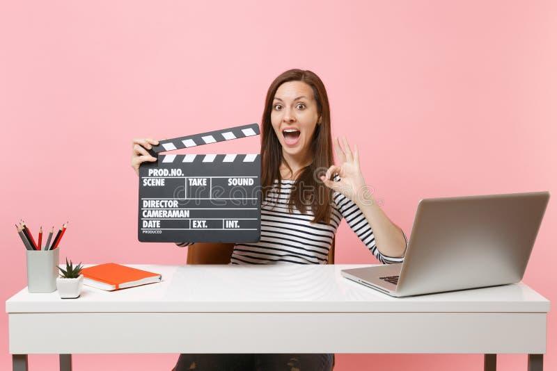 Sinal surpreendido da APROVAÇÃO da exibição da mulher que guarda o clapperboard preto clássico da cinematografia e que trabalha n fotos de stock
