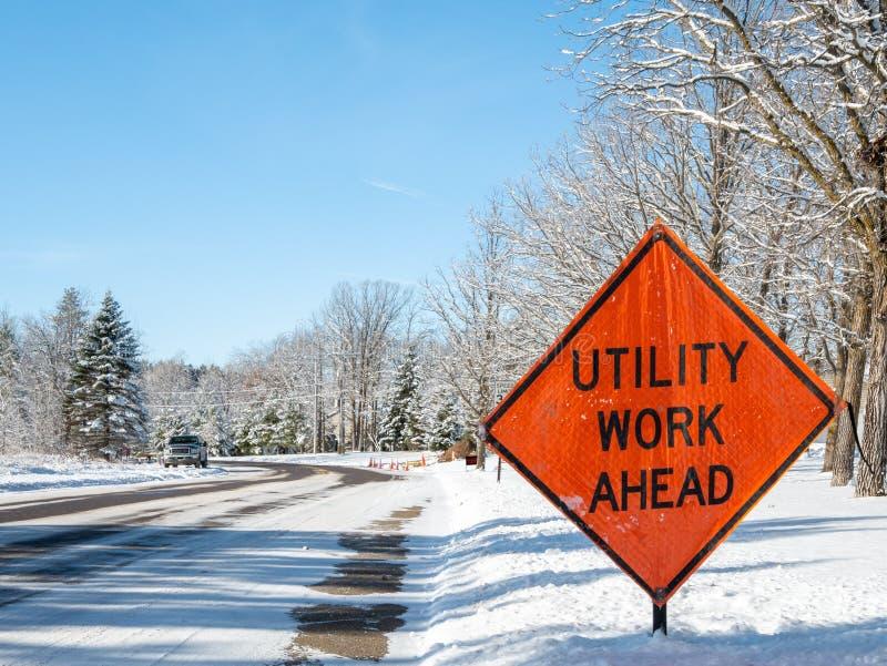Sinal UTILITY WORK AHEAD avisa o trânsito sobre uma zona de trabalho na rua de inverno imagens de stock royalty free