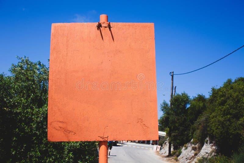 Sinal vazio alaranjado da placa pela estrada Copie o espaço na placa alaranjada Conceito com mensagem na placa vazia Fundo borrad fotografia de stock royalty free