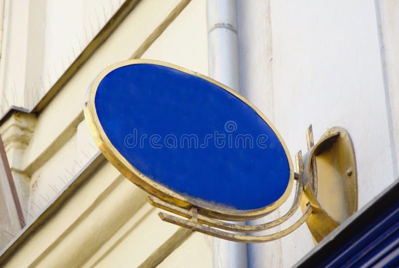Sinal vazio azul com quadro oval dourado na casa fotografia de stock