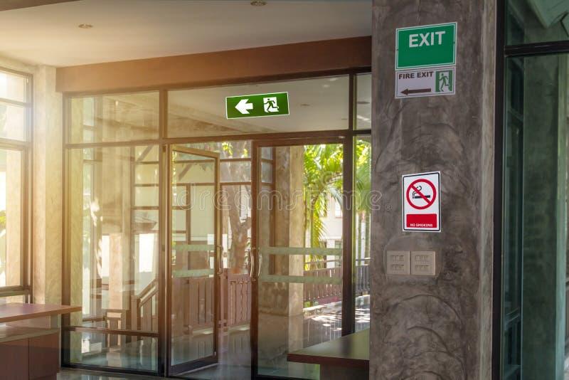 Sinal verde da saída de emergência e para não etiquetar nenhum fumo no canto do resto que mostra a maneira de escapar e advertir  imagem de stock royalty free
