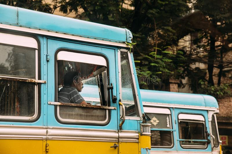 Sinal verde de espera indiano do motorista azul e amarelo da cor do ônibus na estrada em Kolkata, Índia imagens de stock