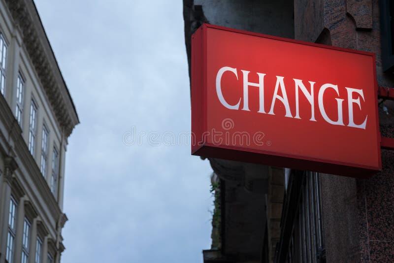 Sinal vermelho com a mudança da palavra escrita, com construções no fundo, quando a noite se aproximar imagens de stock