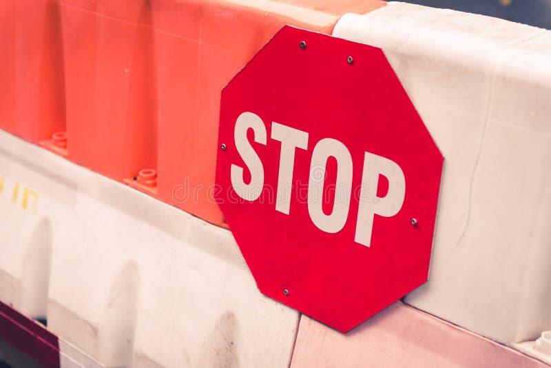 Sinal vermelho da parada em uma placa da estrada do bloco fotografia de stock royalty free