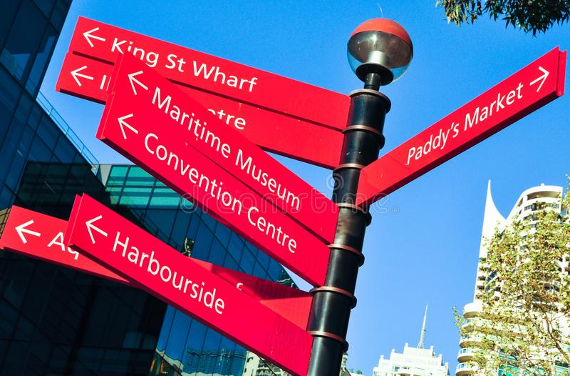 Sinal vermelho da seta dos sentidos que aponta aos lugares famosos em Darling Harbour, Sydney, Austrália imagem de stock