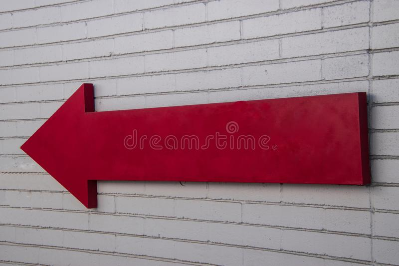 Sinal vermelho de madeira da seta que enfrenta a esquerda em uma parede de tijolo branca fora na luz solar fotos de stock