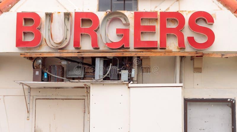 Sinal vermelho retro do hamburguer dos anos 60 na ruína, em umas caixas elétricas cinzentas oxidadas e em uma canalização abaixo  imagens de stock