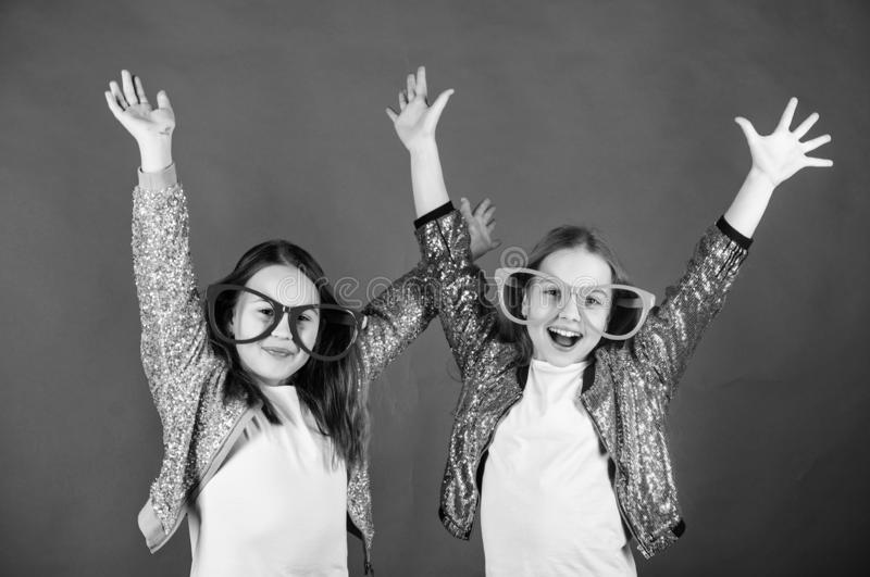 Sincere cheerful kids share happiness and love. Girls funny big eyeglasses cheerful smile. Birthday party. Happy royalty free stock photo