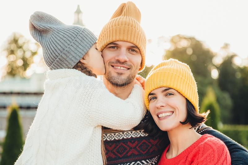 Sincere emotions. Little cute girl in knitted hat and white warm sweater kisses her father with love. Friendly affectionate couple royalty free stock photos