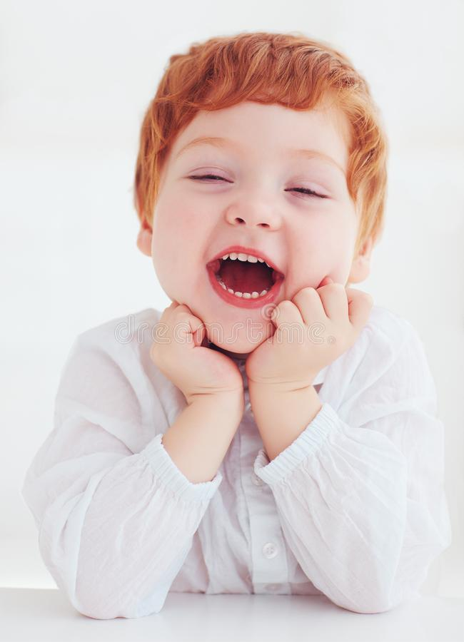 Sincere head portrait of happy redhead toddler baby boy stock photo