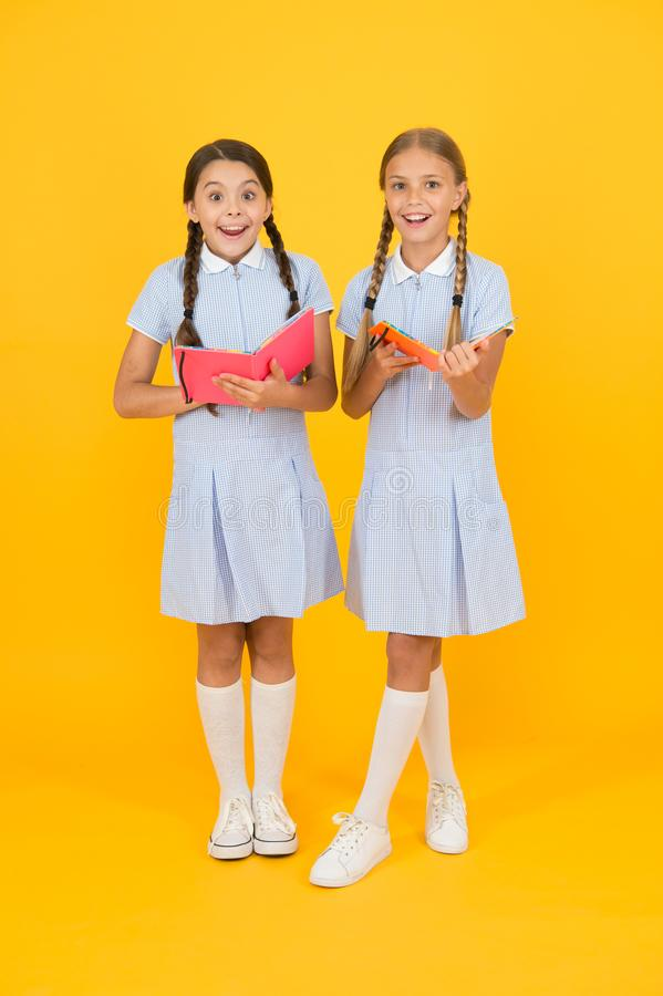 Sincere interest. Little girls with encyclopedia or childrens books. School library. Educational books for school royalty free stock photo