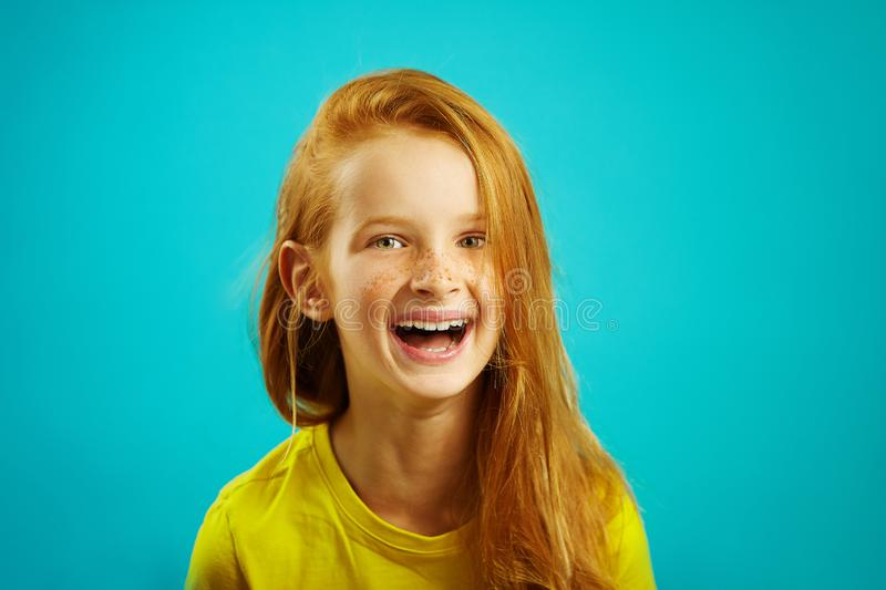 Sincere laughter of children girl with red hair on blue isolated. Happy child expresses a sincere emotion. Sincere laughter of children girl with red hair on royalty free stock photos