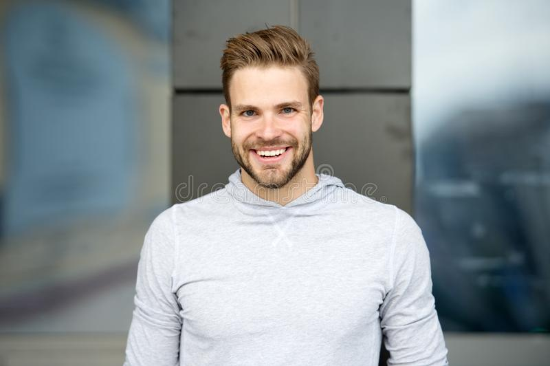Sincere smile concept. Man with perfect brilliant smile unshaven face urban background. Guy happy emotional expression. Outdoors. Bearded and handsome. Man stock image