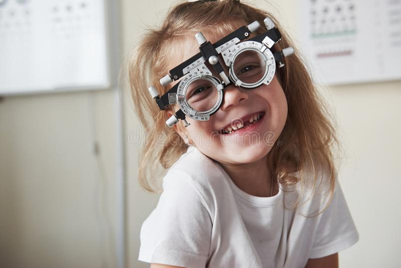 Sincere smile. Focused portrait of little girl in phoropter looking straight into the camera and smiling royalty free stock photo