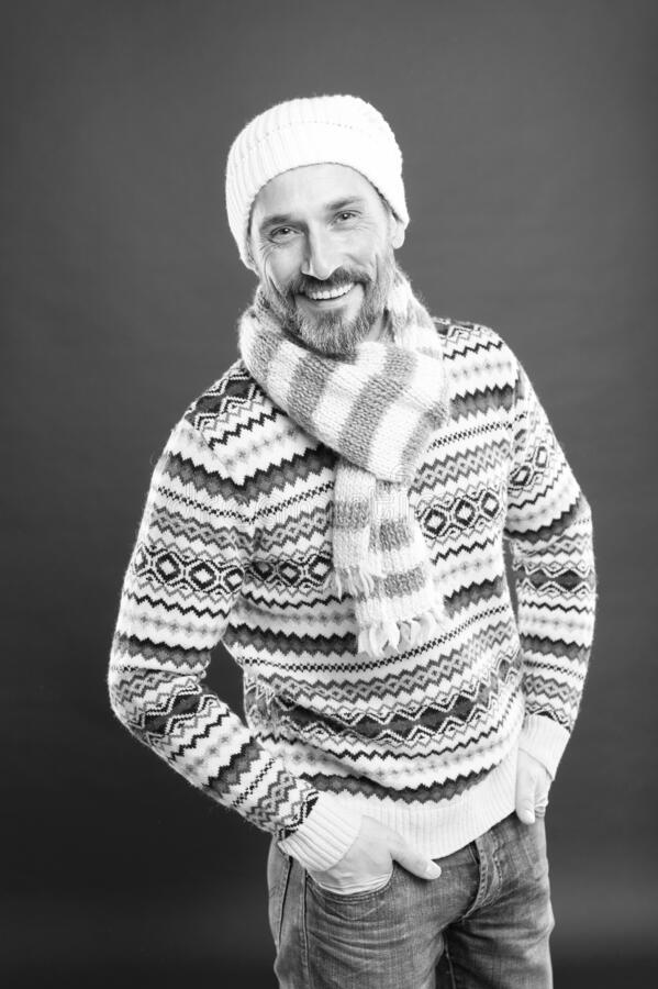 Sincere smile. Handsome bearded man wearing hat and scarf. Winter fashion. Knitted accessories. Winter weather style royalty free stock photography