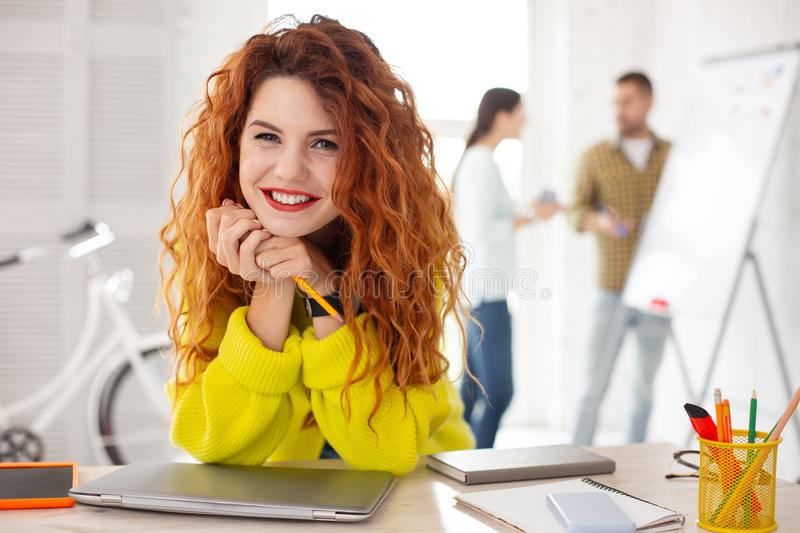 Ginger female employee proposing idea. Sincere smile. Positive female employee holding pencil and grinning to camera stock photos