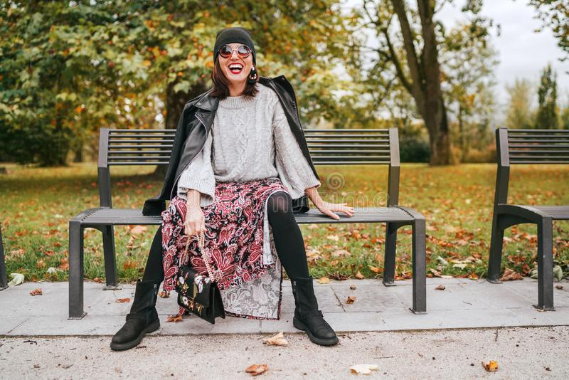 Sincerely laughing female dressed fashion boho style colorful long dress, warm knitted sweater with black leather biker jacket and stock image
