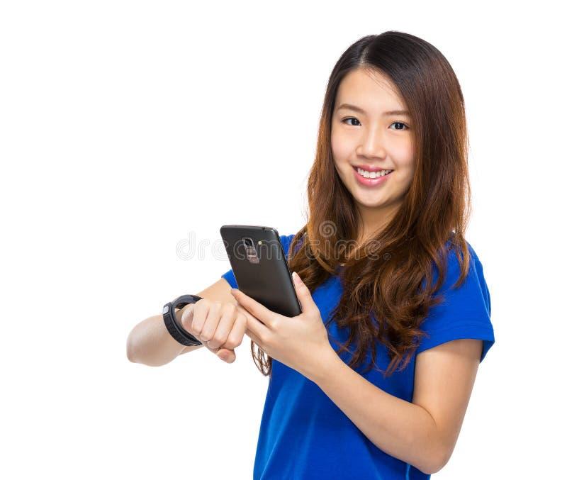 Sincronização do telefone celular do uso da mulher ao relógio wearable fotos de stock royalty free