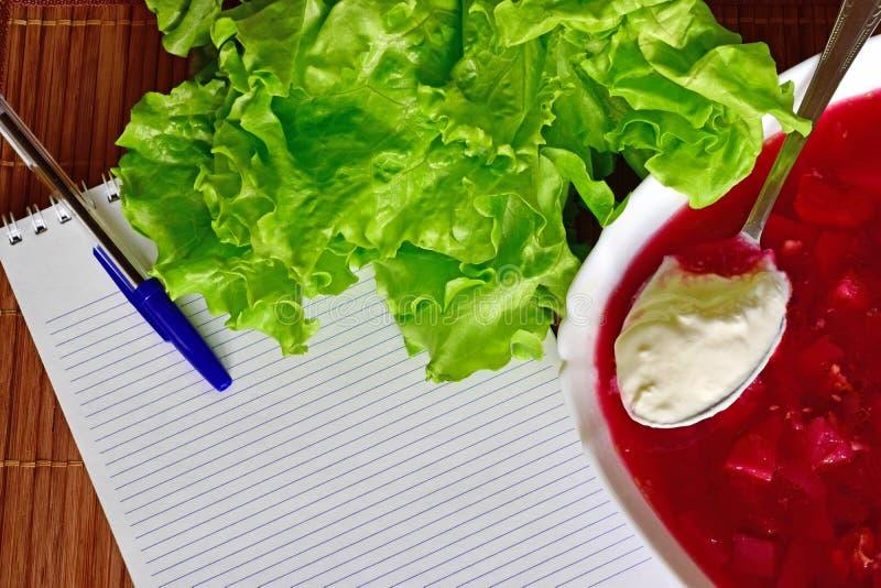 Sind auf dem Tisch Kopfsalat, Notizbuch Platte mit Borschtsch und Löffel mit Sauerrahm stockbilder