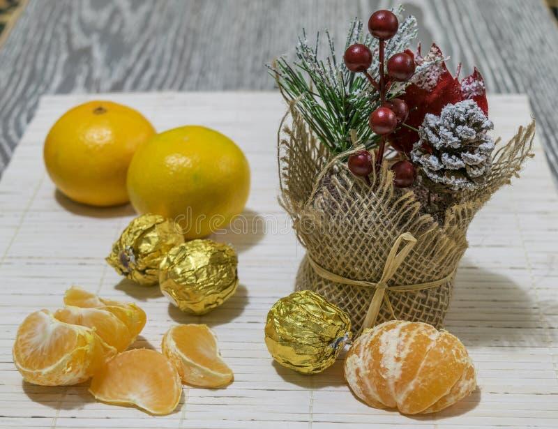 Sind auf dem Tisch Scheiben der Mandarine, der Süßigkeit und der Weihnachtsdekoration stockfotos
