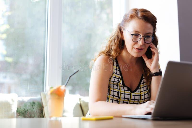 Sind die Arbeitskraft freiberuflich tätig, die ihren Ehemann beim Arbeiten vom Café anruft lizenzfreies stockbild