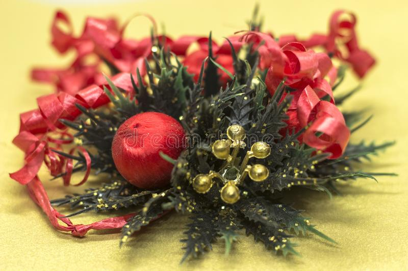 Sine Christmas decoration of red and gold balls and green details on gold background. Shine Christmas decoration of red and gold balls and green details on gold royalty free stock photo