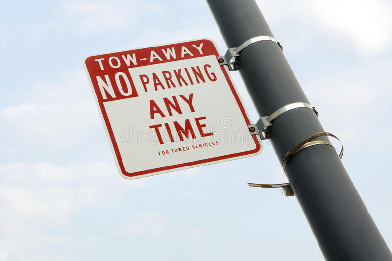 Sing. Close up view of no parking anytime sign on sky back royalty free stock photo