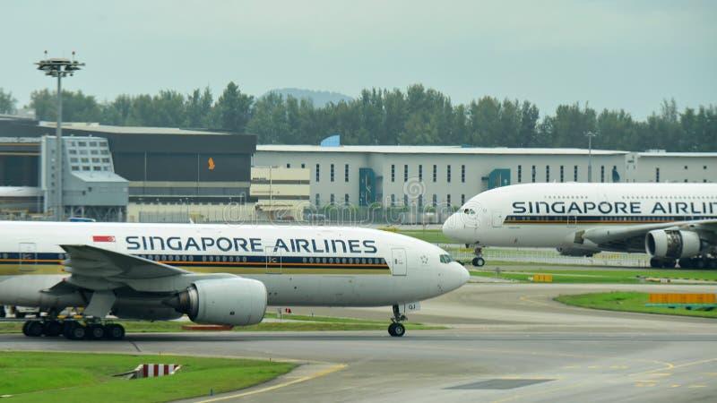 Singapore Airlines Boeing 777-200ER che passa colleghi un jumbo eccellente di Airbus 380 all'aeroporto di Changi immagini stock libere da diritti