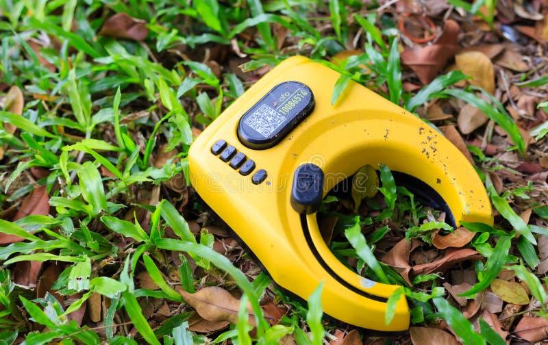 Singapore-26 APR: överge gul färgcykellås på gräsklippning fotografering för bildbyråer