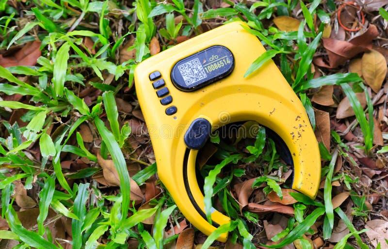 Singapore-26 APR: överge gul färgcykellås på gräsklippning arkivbilder