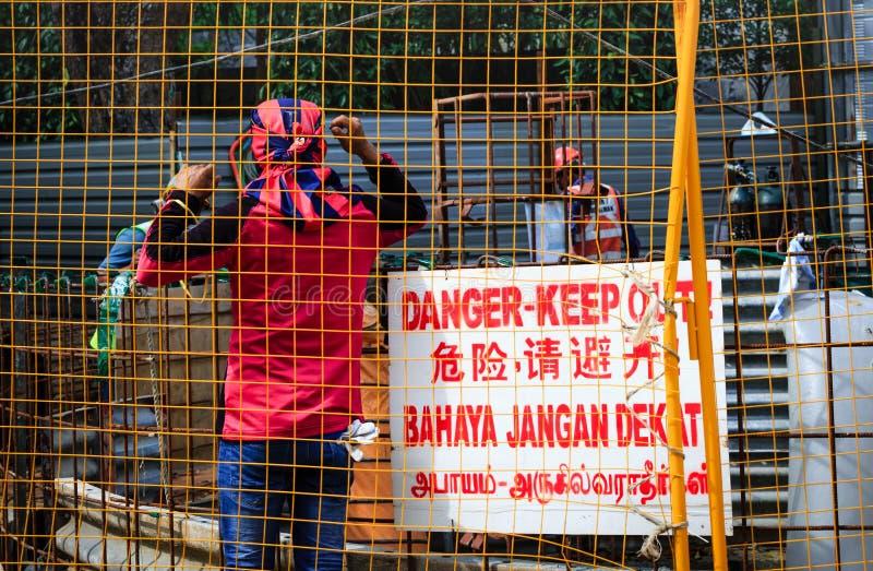 Singapore-02 APR 2019: pracownik jest ubranym ac Milan szalika pracuje w budowie fotografia stock