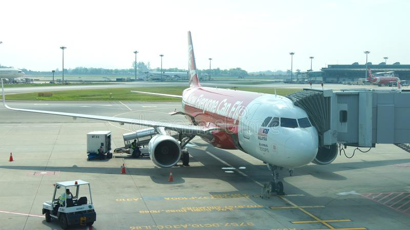 SINGAPORE - APR 4th 2015: Air Asia Airbus A320-200 waiting at the gate at Changi International Airport for passengers stock images