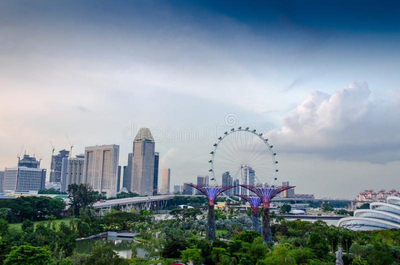 Singapore - April 28, 2014: Singapore Flyer. Singapore Flyer on the horizon against the colorful sky with clouds. In the foreground: Gardens by the Bay, the royalty free stock photos