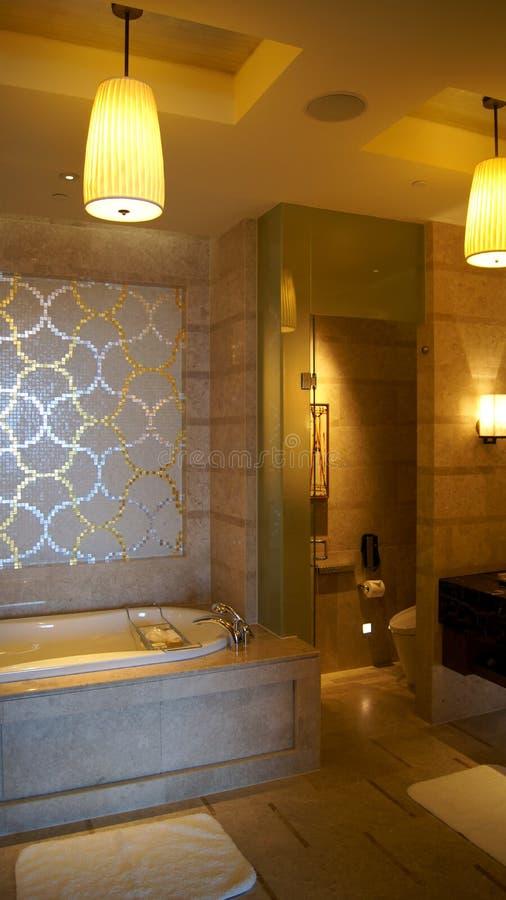 SINGAPORE - 2 april 2015: Grote en modieuze badkamers in bruine en beige kleuren, met ceramisch bad in een luxehotel royalty-vrije stock afbeeldingen
