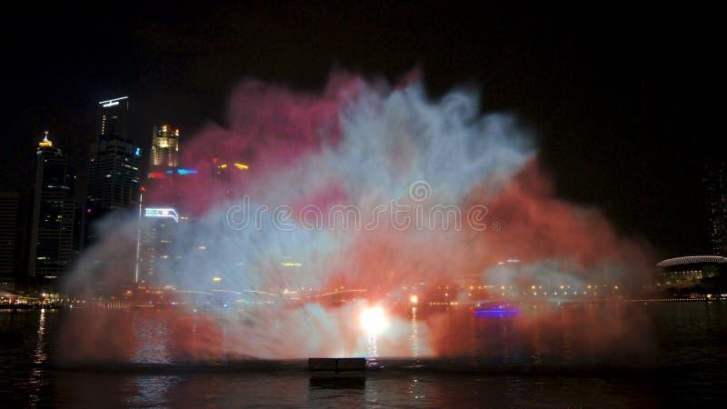 SINGAPORE - APRIL 2nd 2015: Ljuset, vattnet och ljudet visar underbart på Marina Bay Sands på natten royaltyfri fotografi