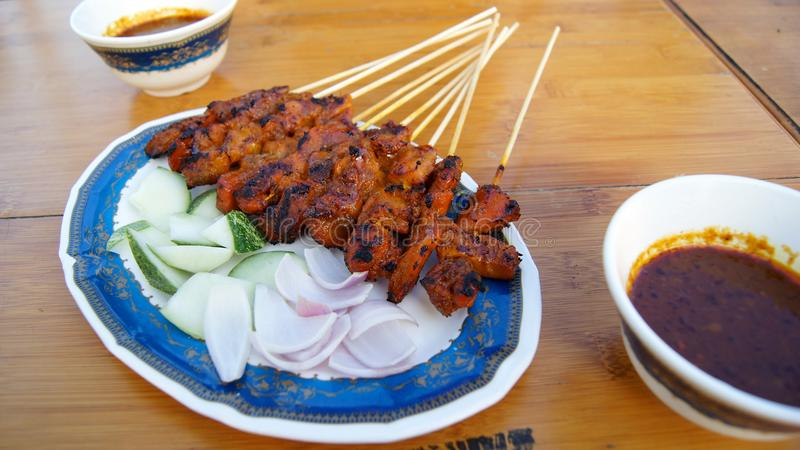 SINGAPORE - APRIL 3rd, 2015: Läckra smakliga steknålar av den fega kocken över varma kol i mat för gata för Singapore ` s Satay royaltyfria bilder