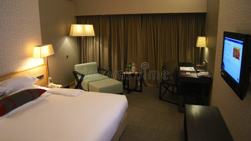 SINGAPORE - APRIL 1st, 2015: lyxigt hotellrum med den moderna inre, en bekväm säng och en stol royaltyfri foto