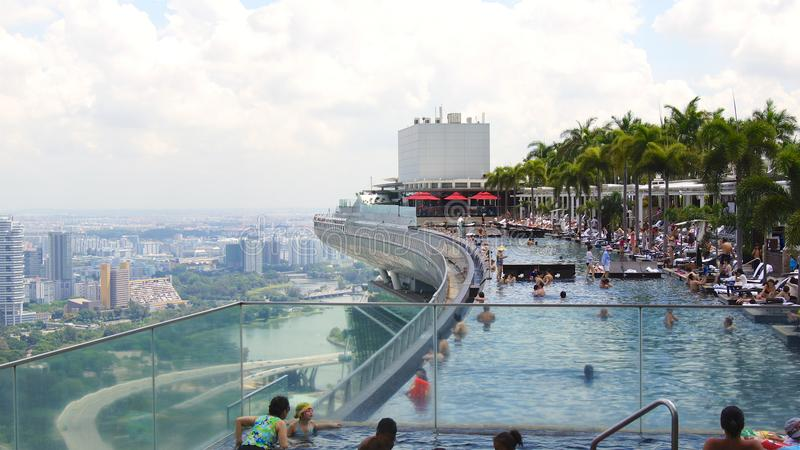 SINGAPORE - APRIL 1st, 2015: Takoändlighetspöl på Marina Bay Sands Skypark, med folk som kopplar av till arkivbild