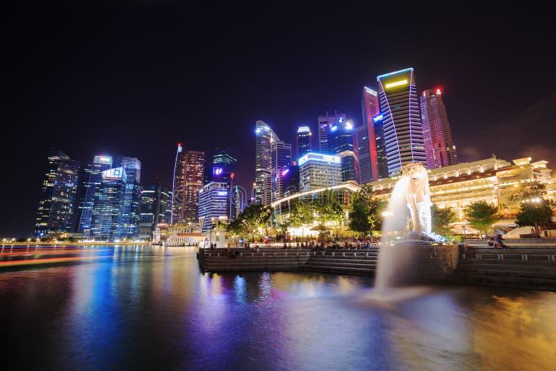 SINGAPORE - AUGUSTI 19, 2017: Merlionen parkerar med turister som besökas på den berömda gränsmärket för natten av Singapore royaltyfri bild