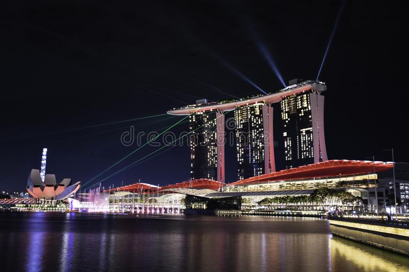 Singapore business building skyline at dawn with reflexion on waterbay in twilight time.Illuminated Marina bay sand laser show at royalty free stock photo